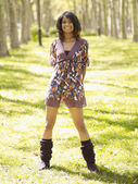 Hispanic woman in dress and leg warmers in park — ストック写真