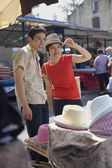 Asian couple trying on hats at market — Stock Photo