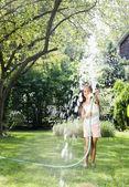 Hispanic girl squirting hose — Stock Photo