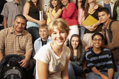 Teenaged girl smiling in front of group of students — Stock Photo