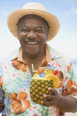 African man holding pineapple drink — Stock Photo