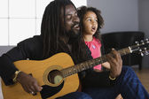 African father playing guitar, daughter singing — Stock Photo