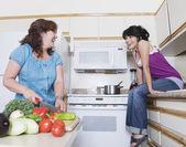 Madre preparando comida y hablando con hija — Foto de Stock