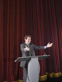 Businessman behind podium on stage — Stock Photo