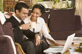 Mixed race couple working on laptop in living room — Stock Photo
