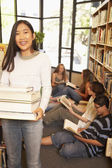 Teenagers with books in library — ストック写真