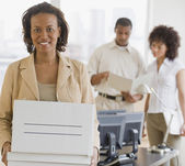African businesswoman holding box — Stock Photo