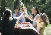 Hispanic family toasting at picnic table — Stock Photo