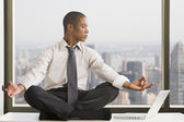 Mixed race businessman practicing yoga at desk — Stock Photo