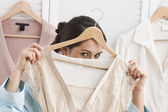 Mixed race woman holding shirt on hanger — Stock Photo