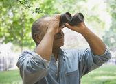 Afrykański mężczyzna patrząc przez lornetki outdoors — Zdjęcie stockowe