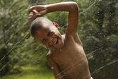 Africký americký chlapec hraje v postřikovače — Stock fotografie