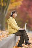 Hispanic woman using laptop outdoors with headphones — Stock Photo
