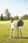 Asian couple on golf course — Stock Photo