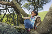 Hispanic girl climbing tree — Stock Photo