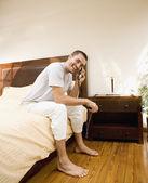 Człowiek siedzi na łóżku, mówiąc na telefon — Zdjęcie stockowe