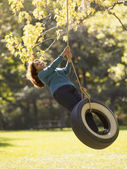 Hispanic woman swinging on tire swing — Stock Photo