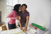 African man measuring wall paper getting kiss from wife — Stock Photo