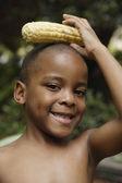 Menino africano-americano segurando a espiga de milho na cabeça — Foto Stock