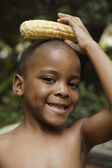 African American boy holding ear of corn on head — Stock Photo