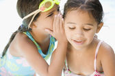 Hispanic girl whispering to sister — Stock Photo