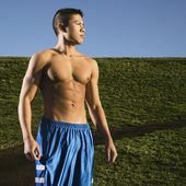 Bare chested Asian man standing in park — Stock Photo
