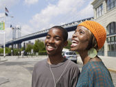African brother and sister sharing earbuds from mp3 player — Stock Photo