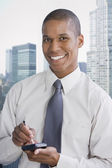 Mixed race businessman using electronic organizer — Stock Photo