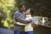 Senior African couple hugging outdoors — Stock Photo