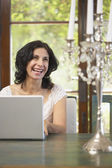 Confident Middle Eastern woman typing on laptop in dining room — Stock Photo