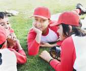 Multi-ethnic boys in baseball uniforms laying on grass — Stock Photo