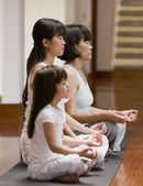 Asian family practicing yoga — Stock Photo
