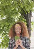 Mixed race woman holding leaf under tree — Stock Photo