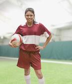 Hispanic girl wearing soccer uniform and holding soccer ball — Stock Photo