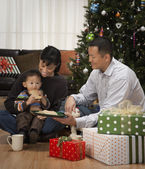 Asian family eating cookies next to Christmas tree — Stock Photo