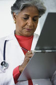 African female doctor writing in medical chart — Foto Stock