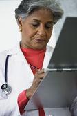 Afrikaanse vrouwelijke arts schrijven in medische grafiek — Stockfoto