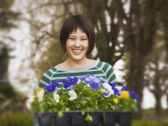 Mixed race woman holding flower plant starters — Stock Photo