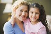 Hispanic mother and daughter hugging and smiling — Stock Photo
