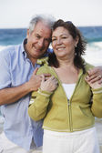 Hispanic couple hugging on beach — Stock Photo