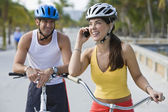 Hispanic woman on bicycle talking on cell phone — Stock Photo