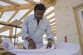 Arquiteto africano olhando plantas no canteiro de obras — Foto Stock