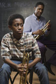 African man and boy holding trumpets in classroom — Stock Photo