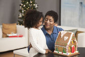 Grandmother and granddaughter looking at gingerbread house — Stock Photo
