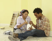 African couple eating take-out in freshly painted room — Stock Photo