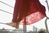 Close up of woman's bare feet standing on railing — Stockfoto