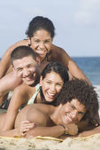 Multi-ethnic friends laying in pile on beach — Stock Photo