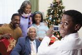 African boy taking Christmas portrait of family — Stock Photo