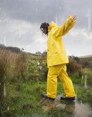 Hispanic woman in rain gear walking in puddle — Stock Photo