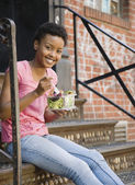 African woman sitting on steps eating salad — Foto Stock